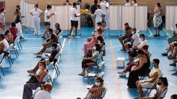 Multitud de jóvenes aguardan sentados tras recibir la vacuna contra el coronavirus