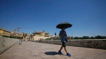 Un turista se resguarda del sol bajo un paraguas mientras camina por el Puente Romano de Córdoba.