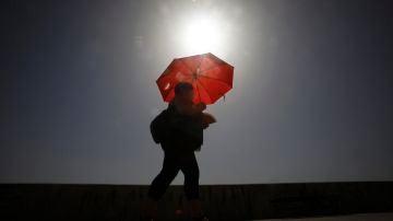 Una mujer camina resguardándose del sol con una sombrilla en Córdoba.