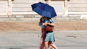 Dos personas evitan el sol con un paraguas en Madrid