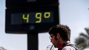Un hombre toma una bebida junto a un termómetro de Córdoba este sábado