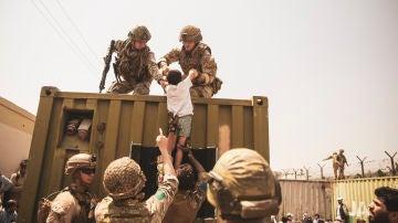 Soldados turcos y estadounidenses ayudan a un niño durante la evacuación en el Aeropuerto de Kabul