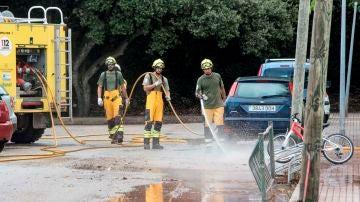 Miembros del IBANAT limpian las calles del fango acumuolado tras el desbordamiento del torrente.