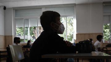 Un niño con mascarilla en un aula.