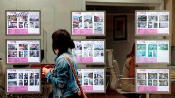 Una persona pasa ante el escaparate de una agencia inmobiliaria (Archivo)
