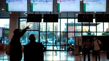Varios usuarios de Renfe esperan n el vestíbulo de la estación de Sants a que aparezca información sobre los horarios de los trenes.